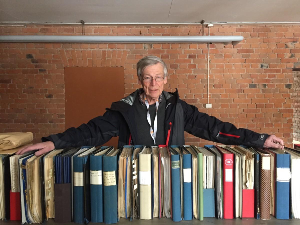Carl-David Söderback vid delar av Reijmyre Glasbruks arkiv.